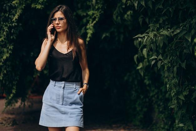 Giovane donna che parla al telefono nel parco