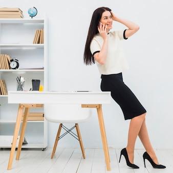 Giovane donna che parla dal telefono in ufficio