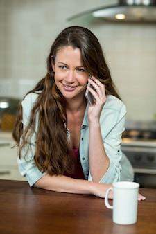 Giovane donna che parla sul telefono cellulare in cucina