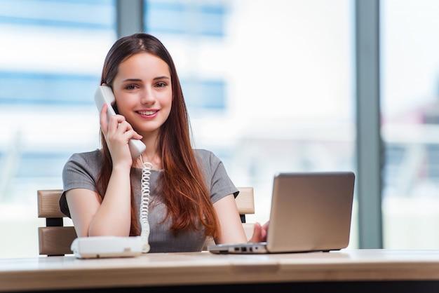 Giovane donna che parla sul telefono in ufficio