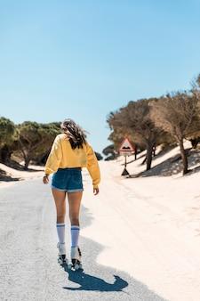 Giovane donna che pattina sui pattini di rullo sul modo pavimentato