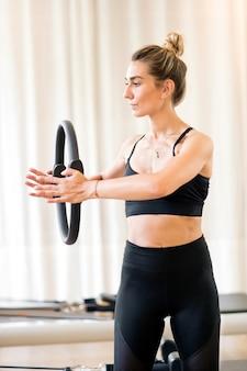 Giovane donna che per mezzo del cerchio magico per il lavoro di braccio