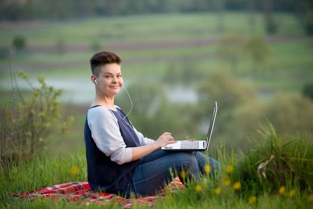 Giovane donna che per mezzo del computer portatile all'aperto
