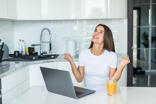 Giovane donna che per mezzo del computer portatile del computer alla cucina che grida fiero e che celebra vittoria e successo molto eccitati