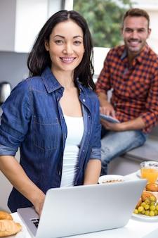Giovane donna che per mezzo del computer portatile e dell'uomo che per mezzo della compressa digitale