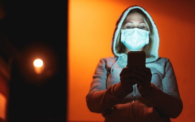Giovane donna che per mezzo del telefono cellulare all'aperto mentre indossando il muschio del fronte di sicurezza durante l'epidemia di coronavirus alla notte