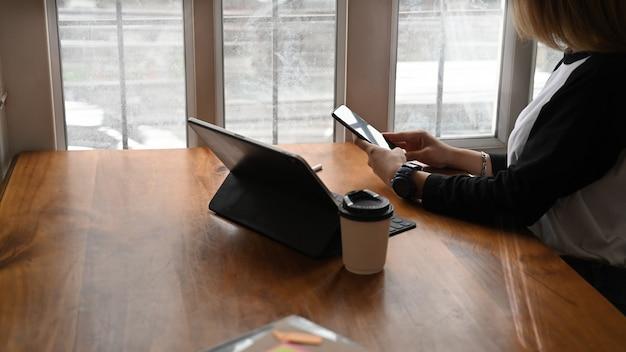 Giovane donna che per mezzo del telefono cellulare sull'area di lavoro dell'ufficio.