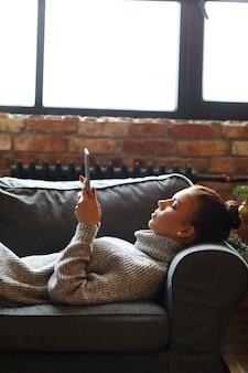 Giovane donna che per mezzo della compressa sul sofà