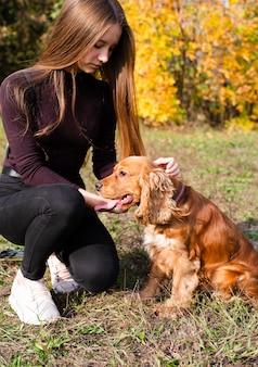 Giovane donna che petting cocker spaniel
