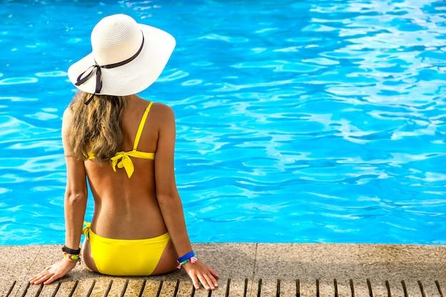 Giovane donna che porta il cappello di paglia giallo che riposa vicino alla piscina con chiara acqua blu il giorno soleggiato di estate.