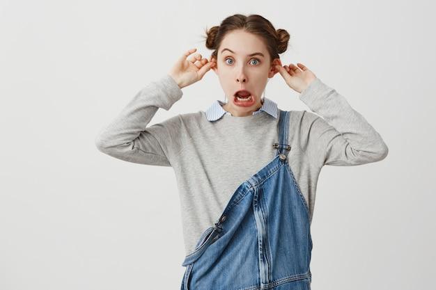 Giovane donna che posa allegro con la bocca aperta che fa smorfie divertendosi. studentessa in abiti casual che scherzano facendo sporgere le orecchie invece di studiare. atteggiamento, concetto di posizione