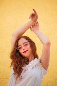 Giovane donna che posa con gli occhiali da sole