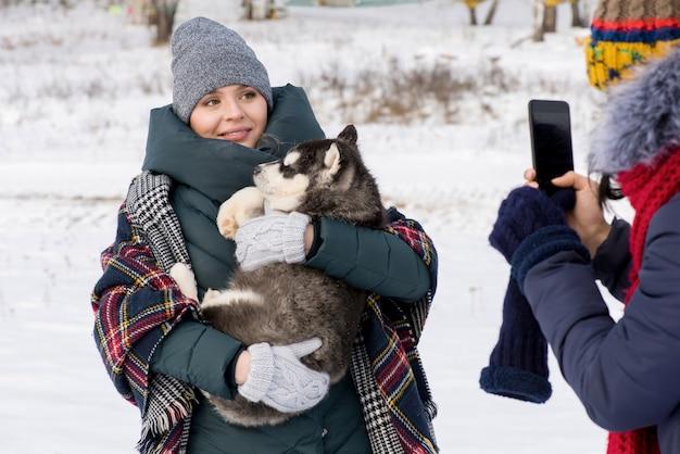 Giovane donna che posa con il cane in inverno