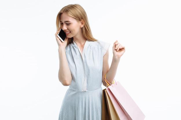 Giovane donna che posa con il telefono, con lo shopping