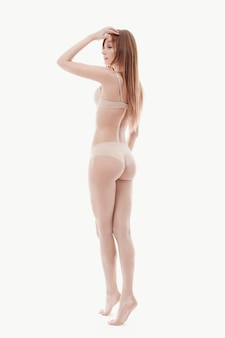Giovane donna che posa in biancheria intima, reggiseno beige e mutandine, pelle perfetta, vista posteriore