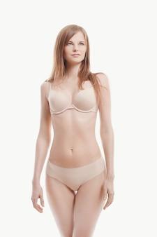 Giovane donna che posa in biancheria intima, reggiseno beige e mutandine, pelle perfetta