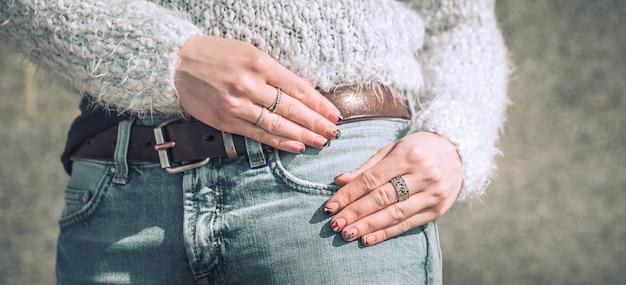 Giovane donna che posa in jeans