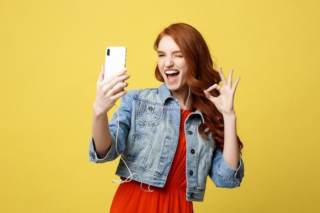 Giovane donna che posa mentre si fotografa sulla macchina fotografica dello smart phone per spirito di chiacchierata