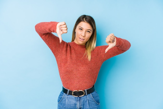 Giovane donna che posa mostrando il pollice giù e che esprime antipatia