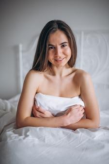 Giovane donna che posa nuda a letto