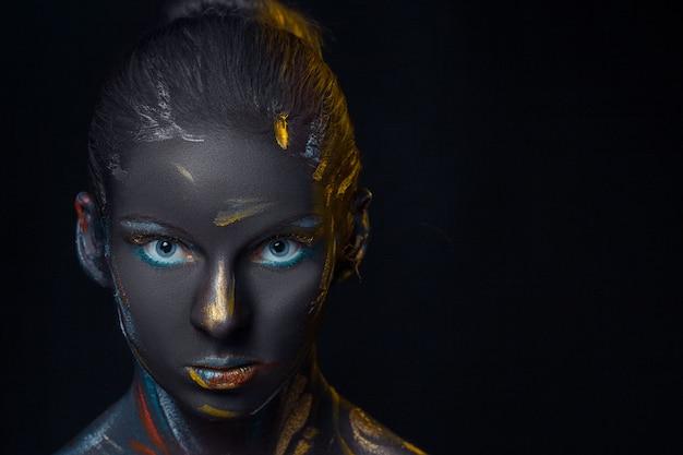 Giovane donna che posa ricoperta di vernice nera