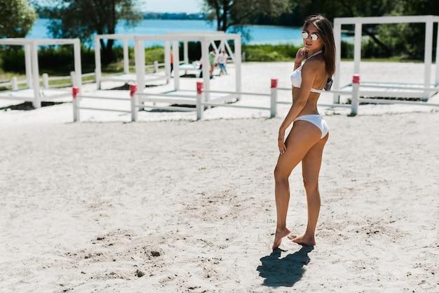 Giovane donna che posa sulla spiaggia sabbiosa