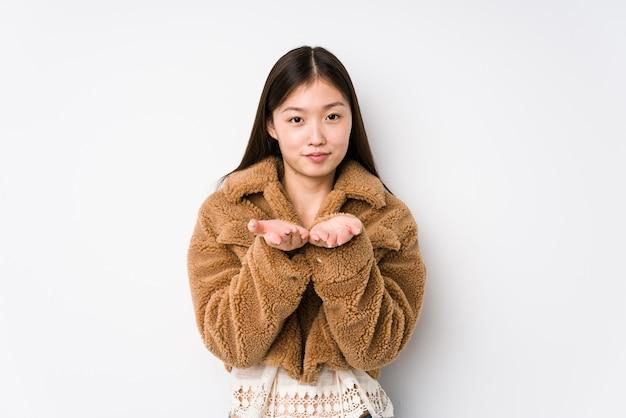 Giovane donna che posa tenendo qualcosa con le palme