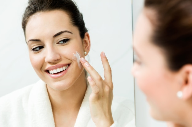 Giovane donna che prende cura della sua pelle in piedi vicino allo specchio nel bagno