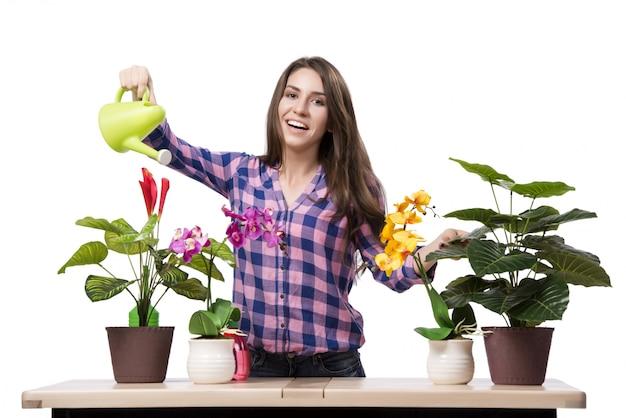 Giovane donna che prende cura delle piante domestiche