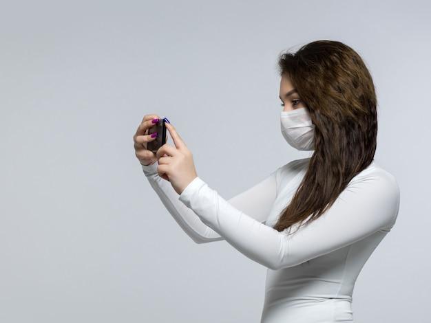 Giovane donna che prende foto se stessa nella maschera medica sterile bianca