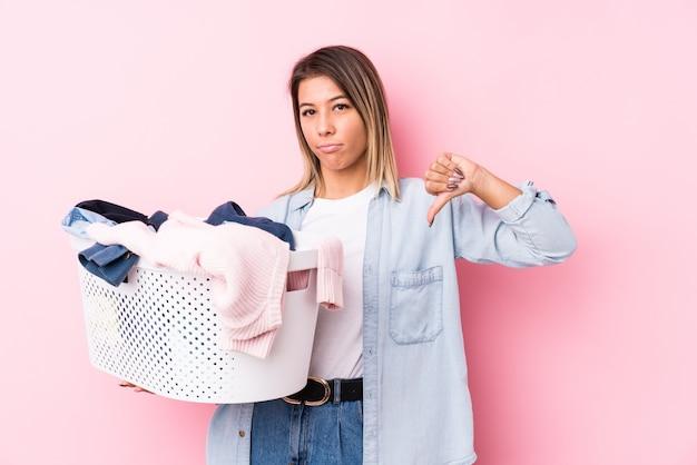 Giovane donna che prende i vestiti sporchi che mostrano un gesto di avversione