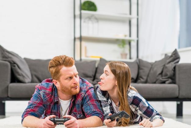 Giovane donna che prende in giro il suo fidanzato mentre gioca al videogioco in salotto