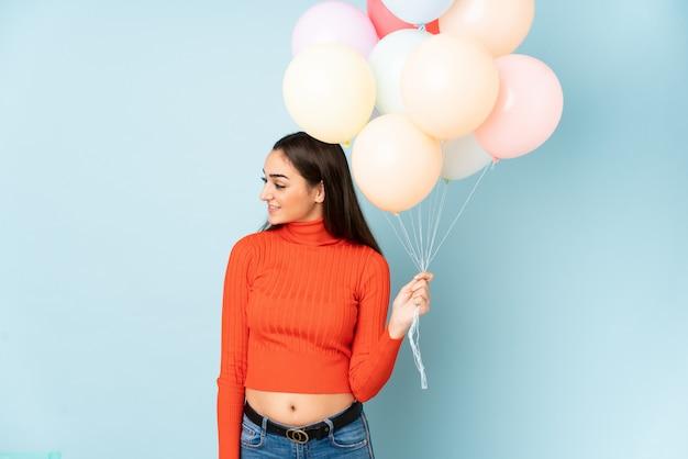 Giovane donna che prende molti palloni isolati sulla parete blu che guarda al lato