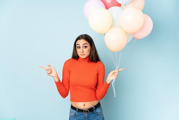 Giovane donna che prende molti palloni isolati sulla parete blu che indica i laterali che hanno dubbi