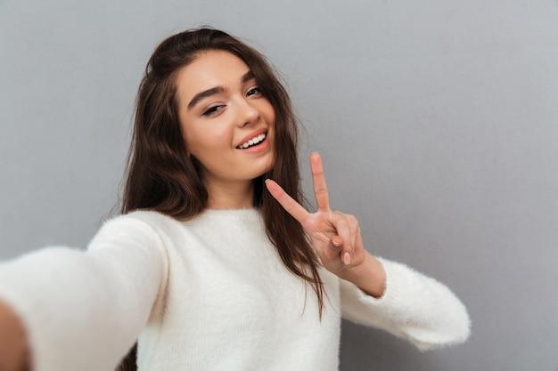 Giovane donna che prende selfie
