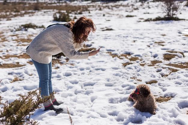 Giovane donna che prende un'immagine con il telefono cellulare a lui cane marrone che si siede sulla neve e che indossa gli occhiali di protezione rossi dello sci