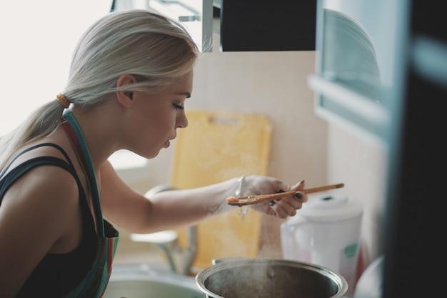 Giovane donna che prepara la zuppa di zucca