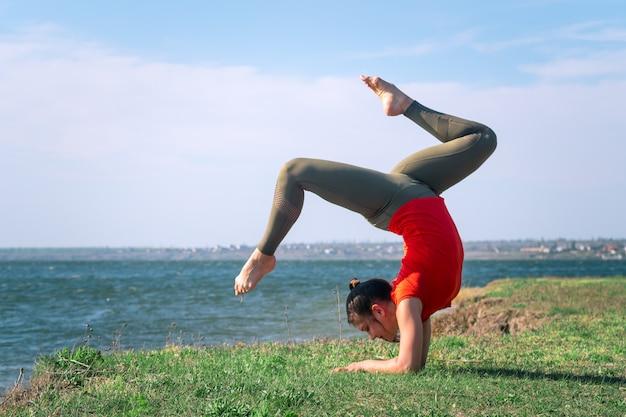 Giovane donna che prepara un'yoga all'aperto