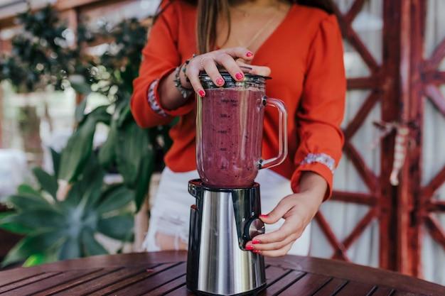 Giovane donna che prepara una ricetta sana di diversi frutti, anguria, arancia e more. usando un mixer. fatto in casa, al chiuso, stile di vita sano