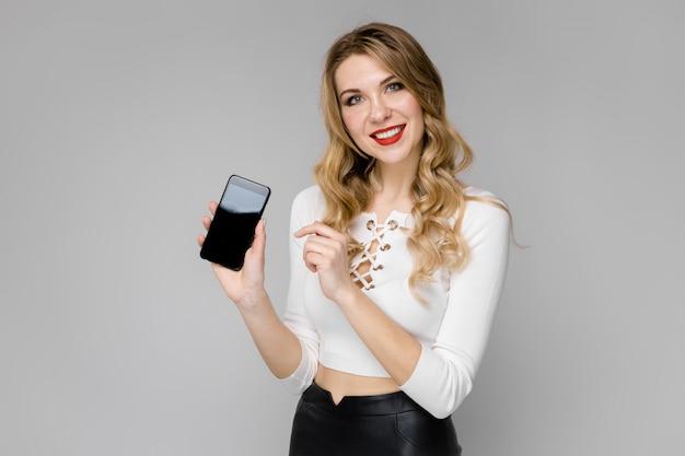 Giovane donna che presenta il telefono