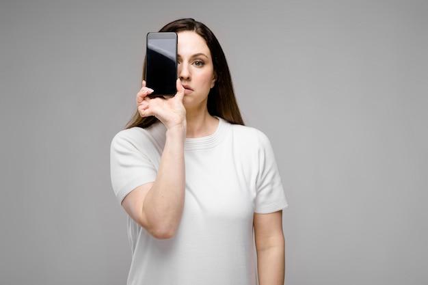Giovane donna che presenta telefono