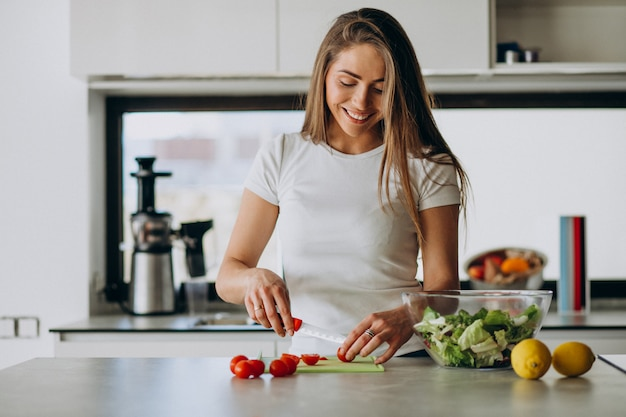 Giovane donna che produce insalata alla cucina