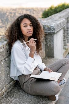 Giovane donna che propone mentre tiene un libro