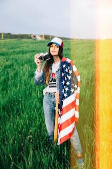 Giovane donna che propone nel campo con la macchina fotografica dell'annata