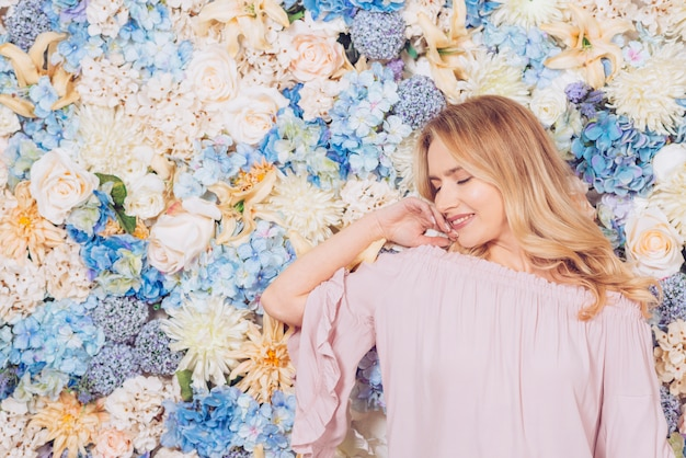 Giovane donna che propone sulla priorità bassa dei fiori