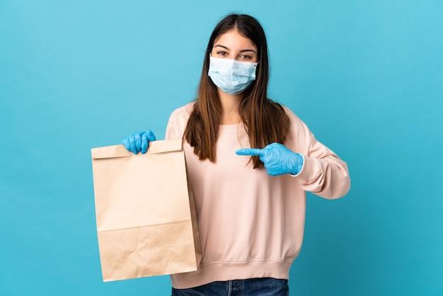 Giovane donna che protegge dal coronavirus con una maschera e che tiene un sacchetto della spesa della drogheria isolato sul blu e che lo indica