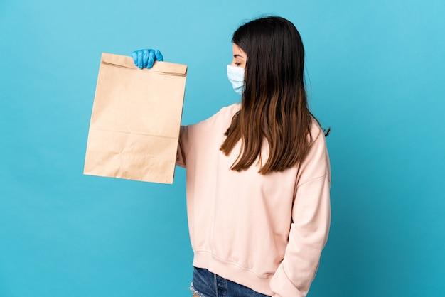 Giovane donna che protegge dal coronavirus con una maschera e che tiene un sacchetto della spesa della drogheria isolato sull'azzurro con l'espressione felice