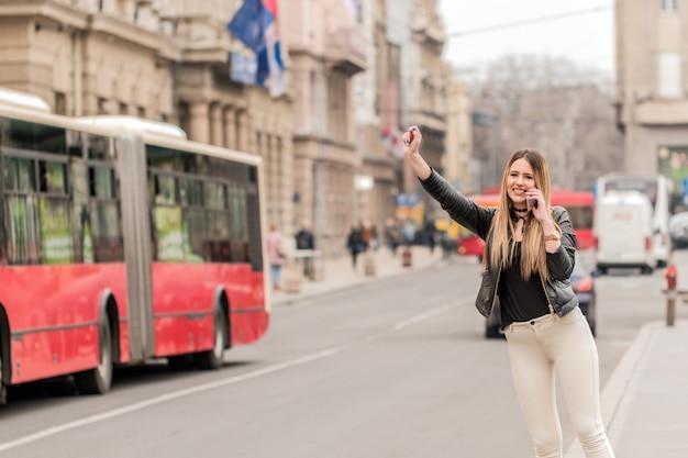 Giovane donna che prova a prendere un taxi