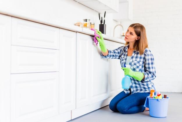 Giovane donna che pulisce la casa