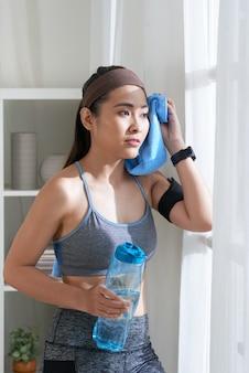 Giovane donna che pulisce testa con l'asciugamano